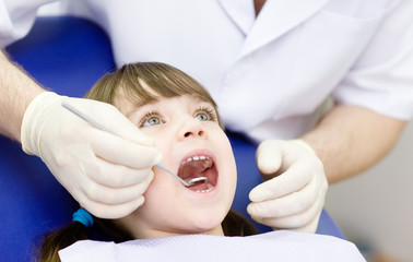 Close-up of little girl opening his mouth wide during inspection