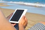 reading on an e-book on the beach
