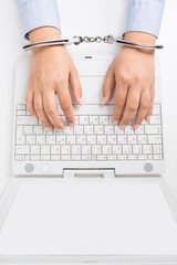 Female hands in handcuffs, with laptop, high angle view