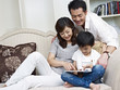 asian family using tablet computer at home