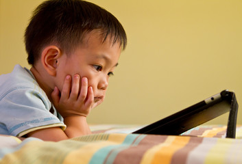Chinese boy using tablet while lying on bed