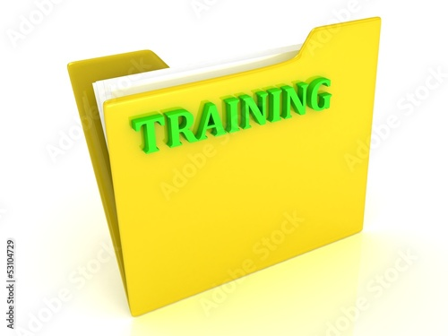 TRAINING bright green letters on a yellow folder with papers