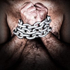 Grunge image of a shirtless man with his hands chained
