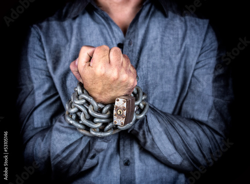 Chained hands of a formally dressed man