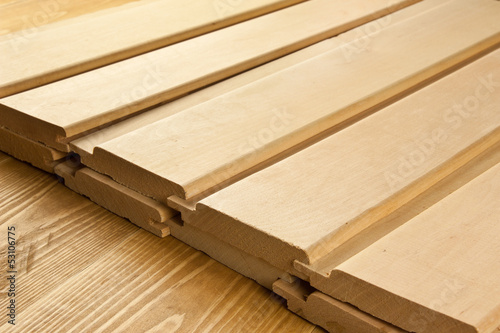 Wood planks are on a wooden board with sawdust