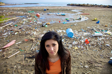 Sad woman in front of dump and dirty beach