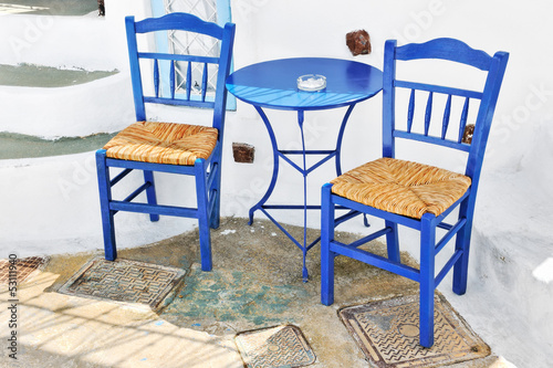 Traditional greek terrace with blue tables and chairs in Pyrgos