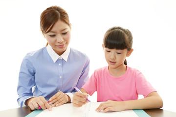 勉強に励む女の子と女性教師