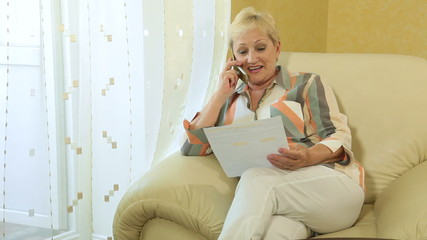 Mature woman with financial document on the phone