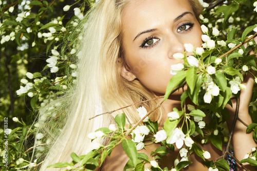 beautiful blond woman with flowers of apple tree