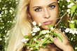 beautiful blond woman with flowers of apple tree. summer