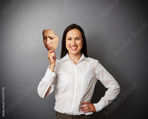 woman hiding her good mood under sad mask