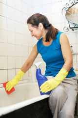 mature woman cleans bathroom with  cleaner