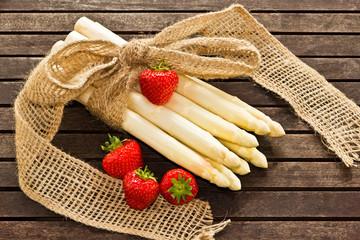 weißer Spargel mit Erdbeeren auf Holz