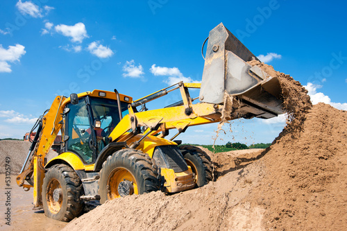 canvas print picture Excavator machine unloading sand during earth moving works