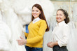 woman with bride chooses white bridal clothes