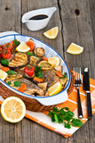 seabass fish baked with vegetables, herbs and lemon