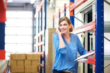 Female worker talking on cellphone in warehouse