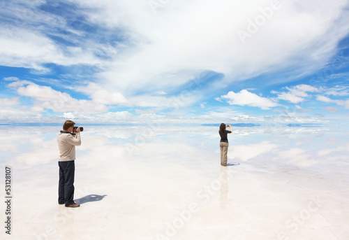 Man and woman take photo of panorama lake Salar de Uyuni