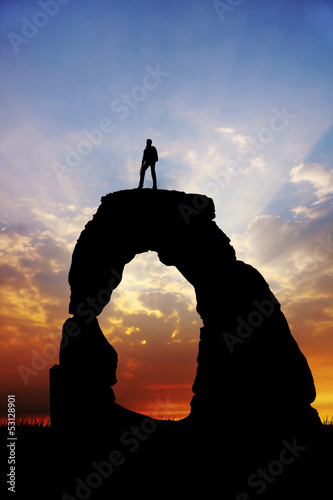 man on rock at sunset
