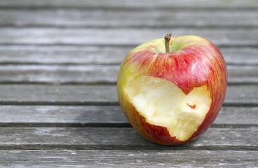 Part eaten ripe apple on wooden boards