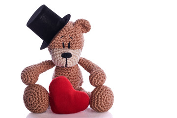 teddy bear with stovepipe and heart pillow