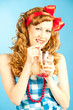 Portrait coquettish Lovely redhead pin-up girl drinks a drink fr