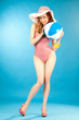 Smiling beautiful girl pin-up in a pink bikini with beach ball