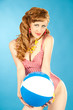 Beautiful girl pin-up in a pink bikini with beach ball