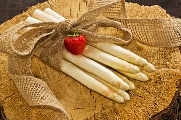 weißer Spargel mit Erdbeere auf einem Holzklotz
