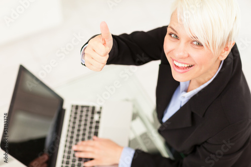 Businesswoman making positive thumb gesture