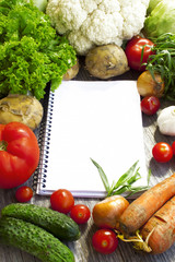 Recipe notebook and fresh vegetable