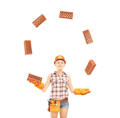 Female construction worker juggling bricks isolated on white bac