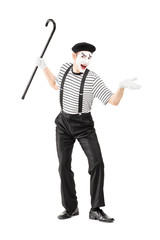 Full length portrait of a mime artist holding a cane and gesturi
