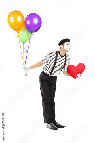 Young mime artist with balloons and red heart giving kisses