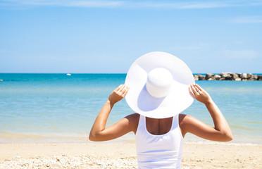 Ragazza con cappello bianco con sfondo di mare rilassandosi