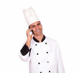 Smiling male chef conversing on cellphone