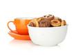 Various cookies in bowl and orange tea cup