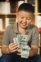 Asian boy with U.S . dollar bank notes