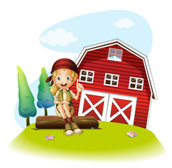 A girl sitting in front of a red barnhouse