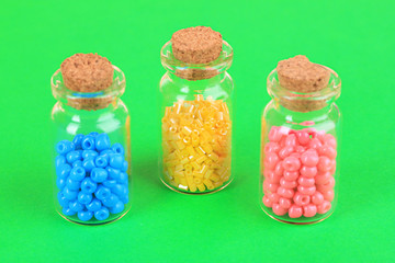 Different colorful beads in bottles on green background
