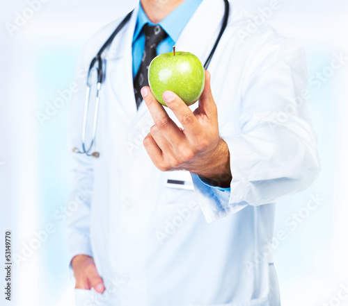 Doctor's hand holding a fresh green apple close-up
