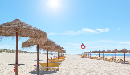 Beautiful sunny beach in Portugal with beach umbrellas and sun b