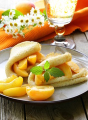 thin pancakes (crepes) with peaches and mint