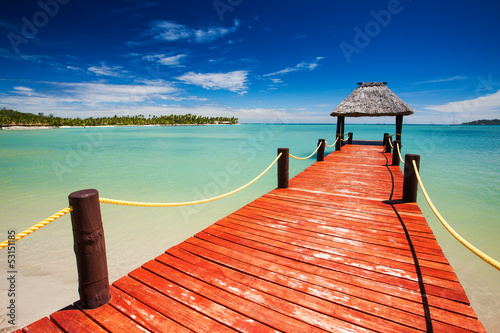 Wooden red jetty extending to tropical lagoon