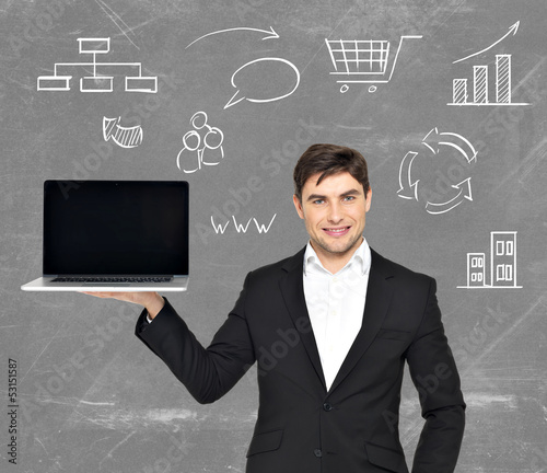 Businessman holds  laptop with icons