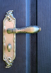 The iron doorhandle on the wooden doors close