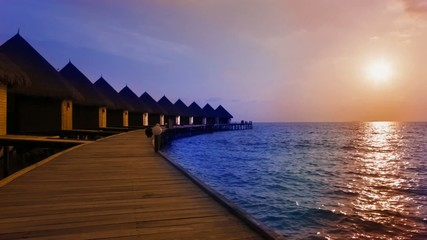 Island in ocean, overwater villas at the time sunset