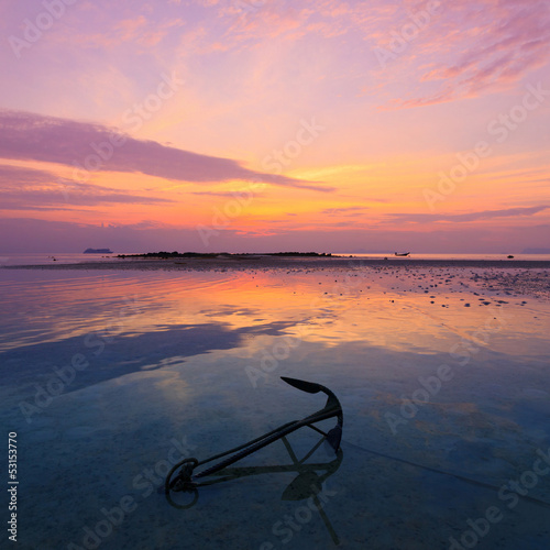 Sunset seascape, old anchor in water during ebb