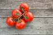 Dewy red tomatoes on the rustic wooden board